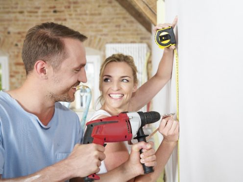 Woman with retractable tape measure and pen and man with drilling machine