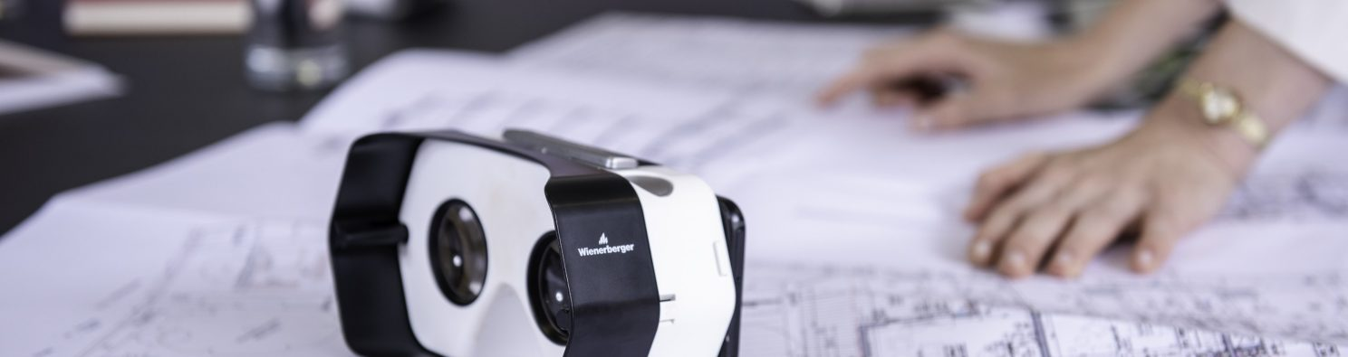 Virtual headset and blueprints at conference table