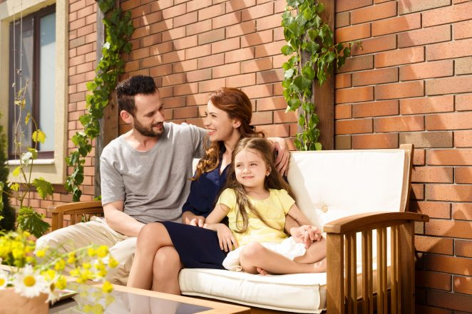 Young family sitting on garden bench in front of brick-lined façade
